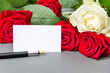 White and red roses with blank white card and pen on a  grey background.