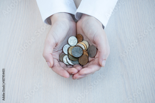 Female hands hold many small coins of rubles