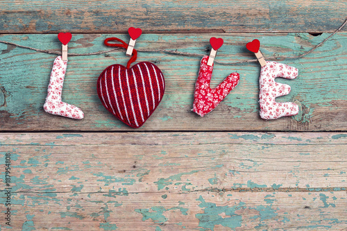 Word love with heart hanging on clothespin on old turquoise wooden background.