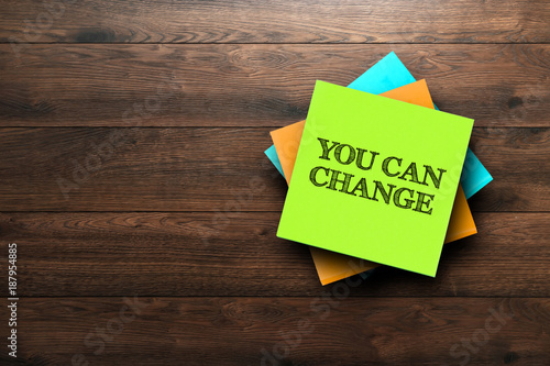 You Can Change, the phrase is written on multi-colored stickers, on a brown wooden background. Live concept