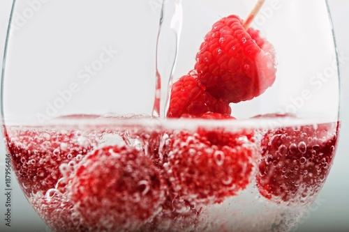 Foto Murales Raspberry with bubbles in glass with pouring water.