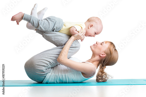 Leinwanddruck Bild young mother does fitness exercises together with baby boy isolated