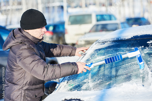 Foto Murales man cleaning car from snow