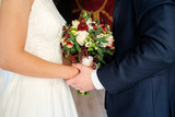 bride and groom play handies and keep bouquet on hands