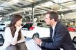 Verkaufsgespräch im Autohandel - Verkäufer berät junge Frau über Kauf eines KFZ´s // Sales talk in the car trade - salesman advises young woman on the purchase of a car