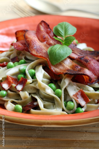 Foto Murales pasta con pancetta e piselli su sfondo tavolo di cucina