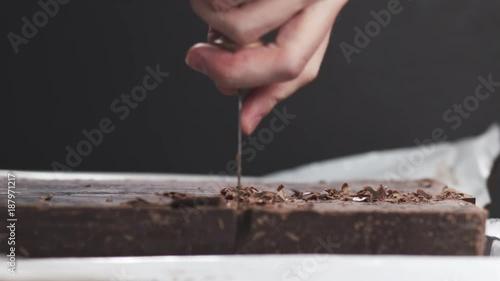 Poster Slow motion closeup young man hands cutting big dark chocolate block with parmesan knife