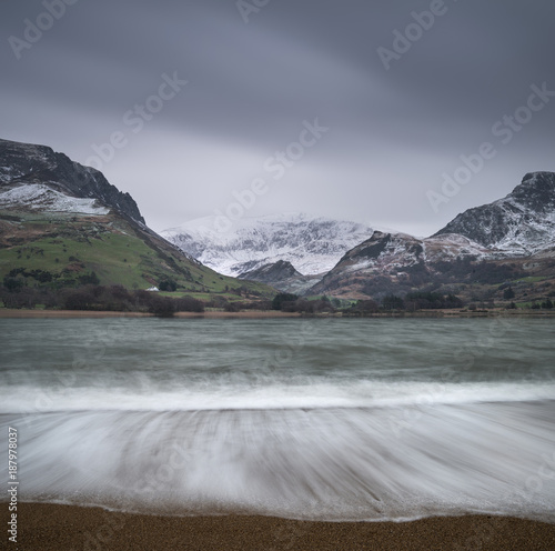 Fotobehang Grijs Beautiful Winter landscape image of Llyn Nantlle in Snowdonia National Park with snow capped mountains in background