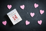 Tear-Off Calendar with Valentine's Day on top and decorative hearts on slate background