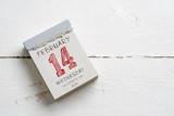 Tear-Off Calendar with Valentine's Day on top on wooden background