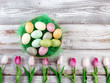 Colorful eggs and tulips for Easter holiday on rustic white wooden background
