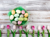 Colorful eggs and tulips for Easter holiday on rustic white wooden background - 187984891
