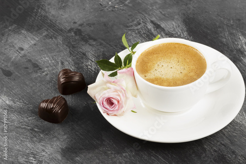 Foto Murales Espresso coffee in a white cup, a pink rose and chocolates on a dark background. Copy space