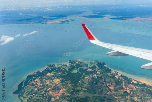 Blue sky, small islands, ocean/sea and a part of airplane engine, top view from an airplane's window.Nice and stunning view during the flight from Phuket to singapore in the morning.