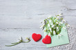 Snowdrops in an envelope and red hearts on a wooden background - 187994027