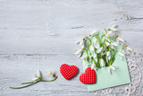Snowdrops in an envelope and red hearts on a wooden background