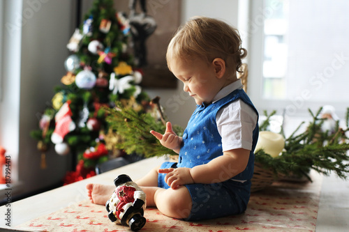 Foto Murales Little boy in suit on the background of Christmas tree