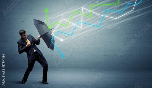 Papiers peints Kiev Business person with umbrella and stock market arrows concept