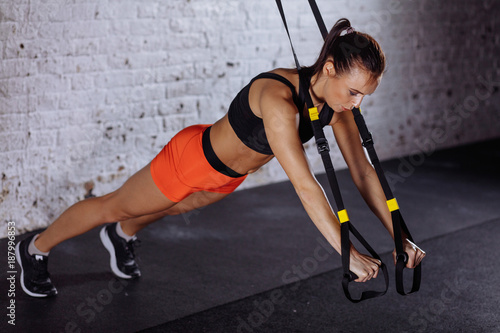 Fridge magnet Women doing push ups training arms with trx fitness straps in gym