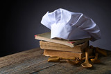 Old culinary books , chef hat and wooden spoons . - 187997826