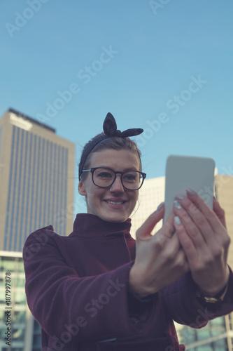 Foto Murales Cute smiley girl using cellphone in modern urban surroundings.