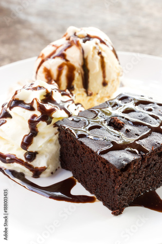 Brownie served with ice cream and whipped cream on white plate. Topping with chocolate sauce.