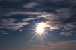the sun with rays on the cloudy sky.