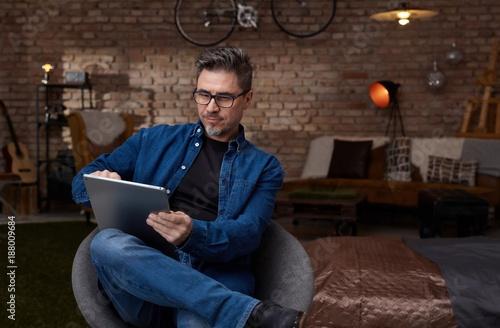 Foto Murales Older white man sitting in dark room using tablet