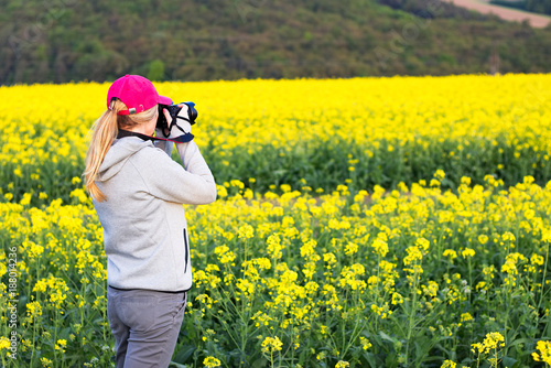 Foto op Plexiglas Geel Woman with camera taking pictures of the countryside.