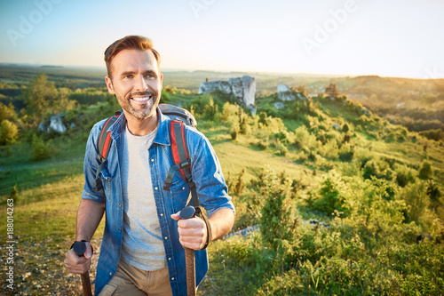 Smiling man hiking in the mountains using poles and looking away