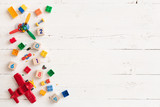 Top view on multi-color toy bricks on white wooden background. Children toys on the table. - 188020459