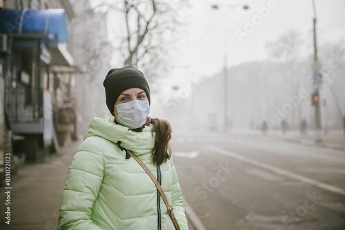 the girl is standing by the road in a protective medical mask.