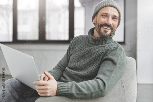 Pleased male freelancer with specific appearance happy as installs new antivirus system on laptop, enjoys free time in comfortable armchair. Glad European man browses internet websites online