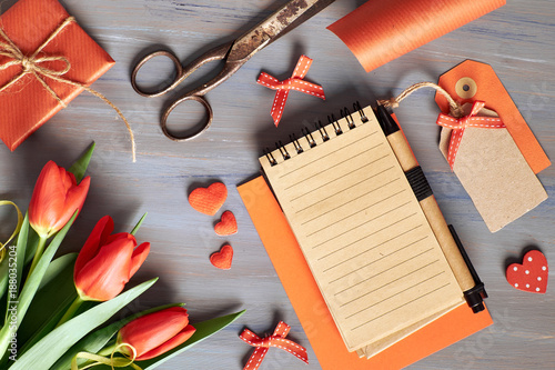 Foto Murales Blank notebook, wrapped gift, wrapping materials and fresh orange tulips on wooden table