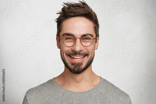 canvas print picture Headshot of satisfied cheerful handsome man grins at camera, glad to find suitable well paid job, isolated over white concrete background. People, positive emotions and facial expressions concept