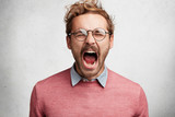 Emotional mad crazy young male screams loudly and with anger, being stressed and in panic, frowns face, isolated over white concrete wall. Negative human emotions, feelings, reaction concept - 188038875