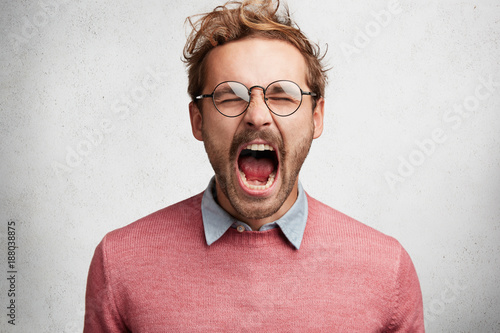 Foto op Aluminium Kasteel Emotional mad crazy young male screams loudly and with anger, being stressed and in panic, frowns face, isolated over white concrete wall. Negative human emotions, feelings, reaction concept