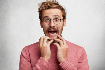 Worried scared fashionable man looks with terrified expression, keeps arms on chin, dressed in pink sweater, isolated over white background. Emotional bearded young guy receives unexpeted news © Wayhome Studio