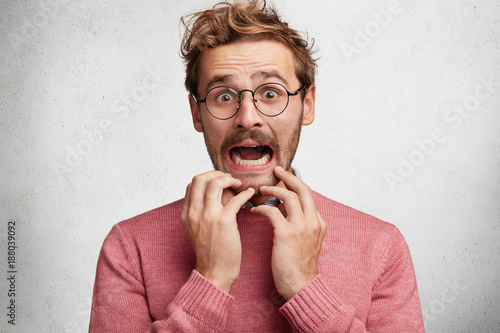 In de dag Kapsalon Worried scared fashionable man looks with terrified expression, keeps arms on chin, dressed in pink sweater, isolated over white background. Emotional bearded young guy receives unexpeted news