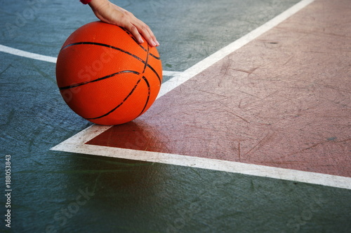Fotobehang Basketbal single orange basketball with woman player hand on green red sport gymnasium floor background