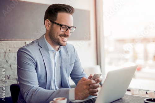Young businessman working in office, sitting at desk.