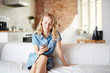 Young blonde in denim T-shirt dress sitting on sofa at home and searching in smartphone