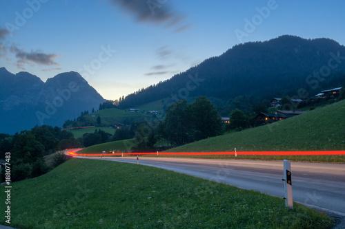 Keuken foto achterwand Nachtblauw Road in alpine countryside at night, red traffic lights