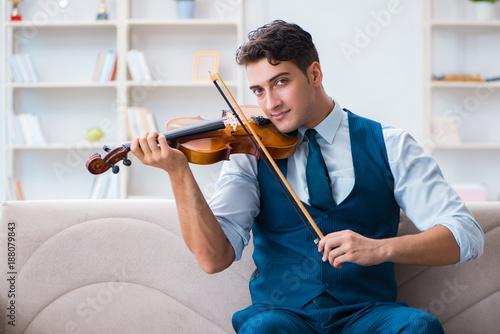 Foto Murales Young musician man practicing playing violin at home