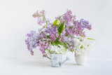 Bouquet of lilac in a vase on a light background - 188080246