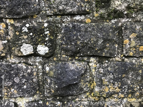 Foto op Canvas Stenen old wall of black stones