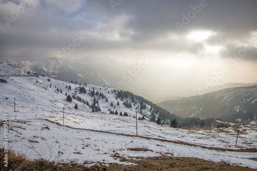 Papiers peints Taupe sunset in the snowy mountains with low clouds