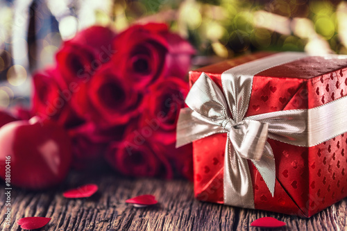 Valentine wedding concept. Bouquet of roses and wrapped gift with red hearts on wooden table