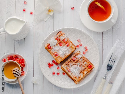 Papiers peints Vienne Delicious mouth-watering Viennese waffles with honey and pomegranate seeds on a white plate, light wooden background