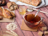 Grain bread with honey and nuts, a mug of tea brown sugar on dark wooden background - 188108026